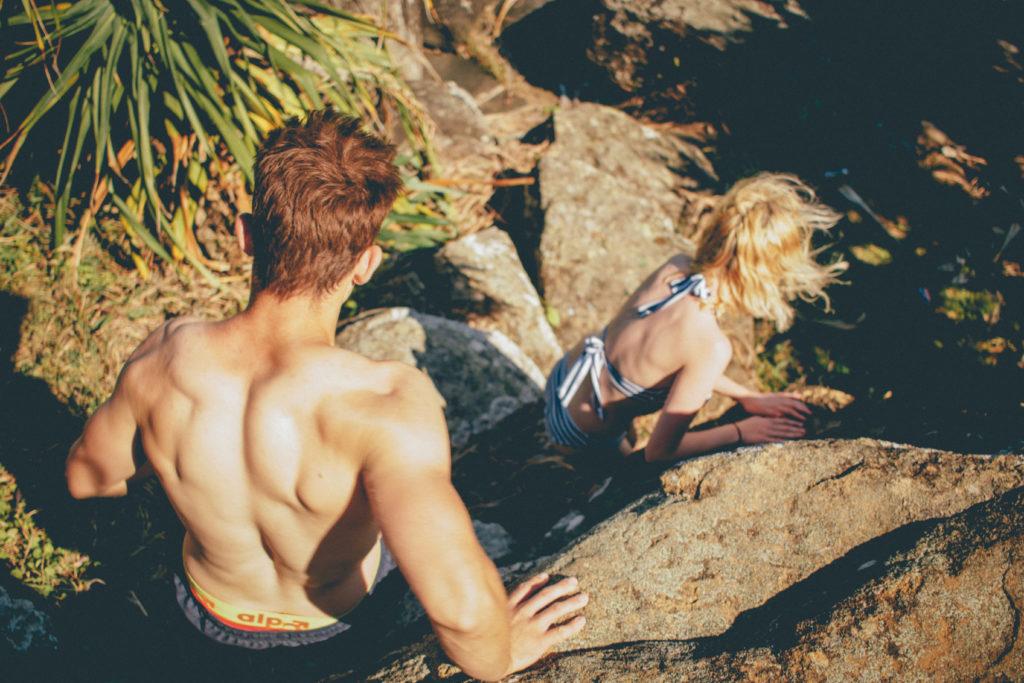 Couple Climbing Down the Rocks