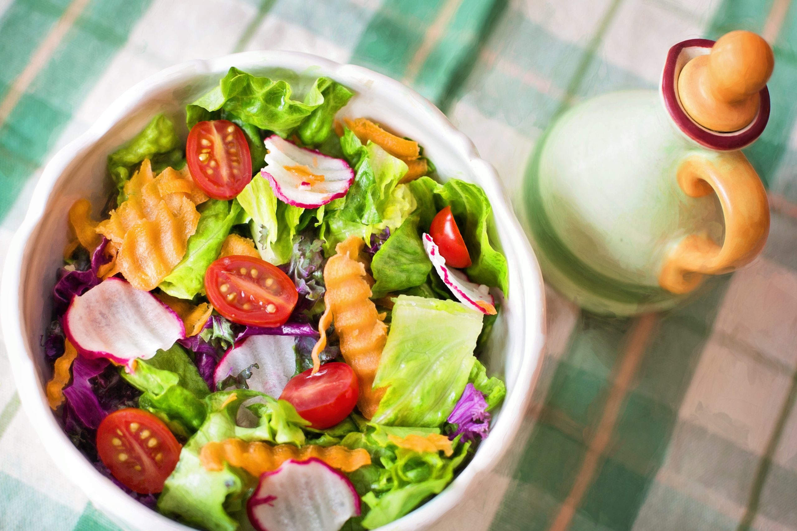 Healthy bowl of salad next to dressing